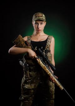 Une fille sexy en salopette militaire d'airsoft pose avec un fusil de sniper sur un fond sombre