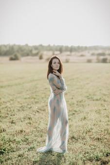 Fille sexy en sous-vêtements seins nus dans le champ en été à l'extérieur. ajout de l'effet d'un petit grain de film