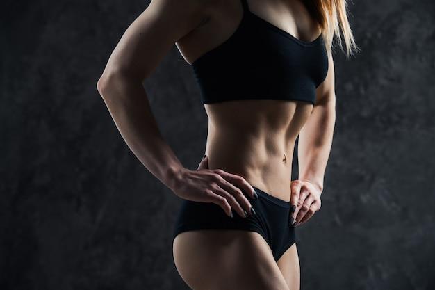 Fille sexy de sport avec gros ventre musculaire dans un vêtement de sport noir sur fond noir.
