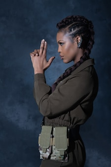Fille sexy vêtue d'une combinaison kaki de style militaire posant en studio