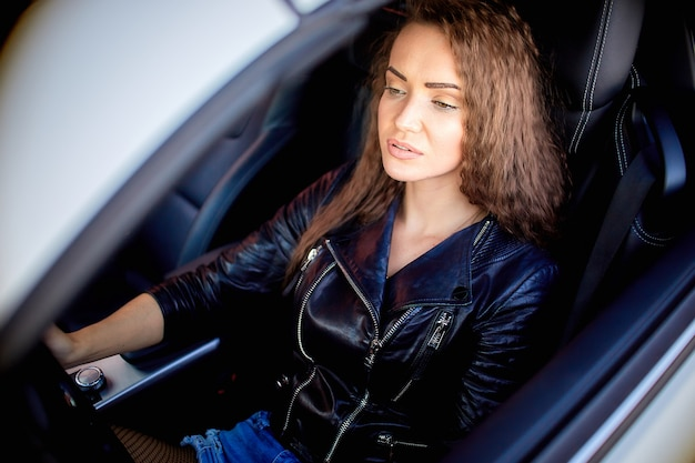 Une fille sexy vêtue d'une veste en cuir, d'un short en jean et de collants noirs dans le filet s'assoit au volant d'une voiture