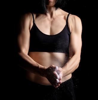 Fille avec une silhouette sportive vêtue d'un haut noir applaudit dans ses mains avec de la magnésie blanche