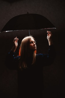Fille de silhouettes sous un parapluie dans une lumière sombre
