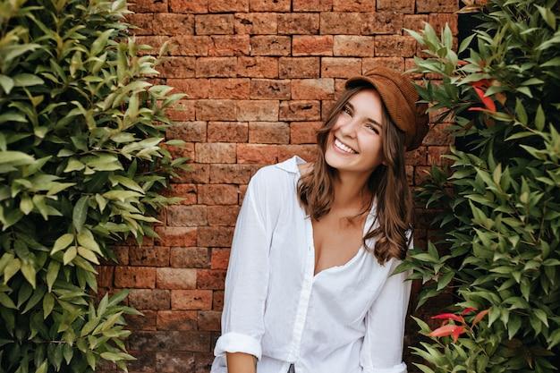 Fille sincère en bonnet marron et chemisier blanc rit, appuyée sur une clôture en brique. plan d'une femme bronzée avec un sourire blanc comme neige parmi des buissons à feuilles persistantes.