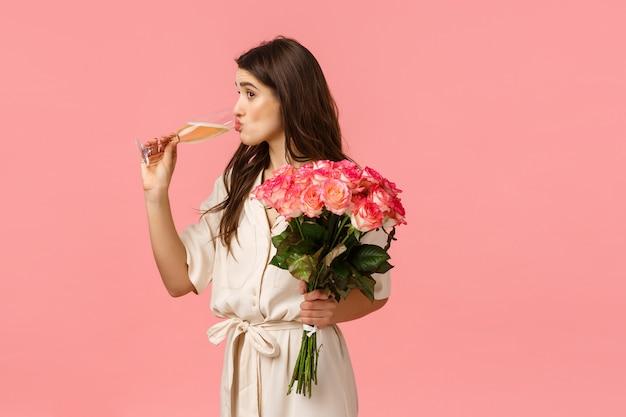 Fille sirotant du champagne dans un verre en regardant quelqu'un, vêtue d'une robe élégante, célébrant, faisant la fête, recevant des roses, bouquet de fleurs, debout sur fond rose intrigué et amusé