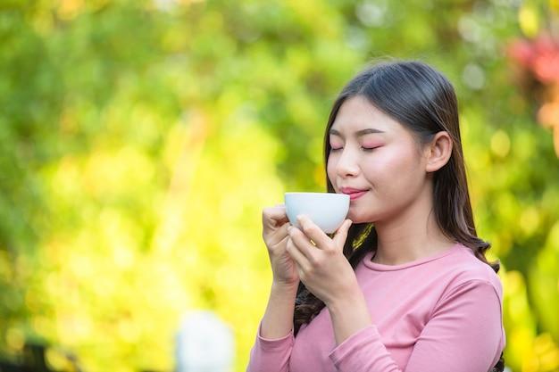 La fille sirote un café avec plaisir au café.