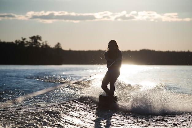 Fille de ski nautique avec la lueur du soleil derrière elle, lac des bois, ontario, canada