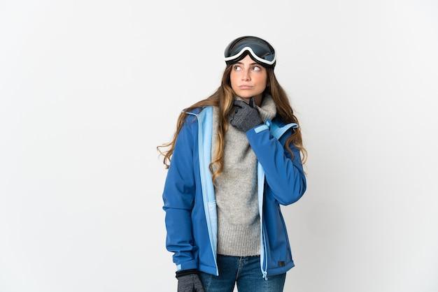 Fille de skieur avec des lunettes de snowboard sur blanc ayant des doutes