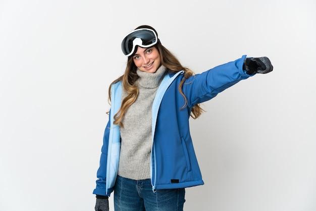 Fille de skieur avec des lunettes de snowboard sur blanc donnant un geste de pouce en l'air