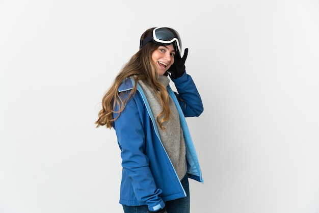 Fille de skieur avec des lunettes de snowboard sur blanc en écoutant quelque chose en mettant la main sur l'oreille