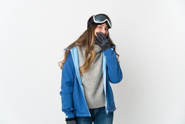 Fille de skieur avec des lunettes de snowboard sur blanc heureux et souriant couvrant la bouche avec la main