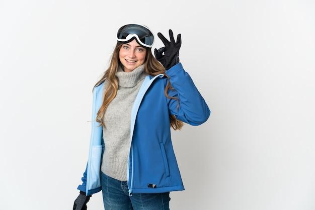 Fille de skieur avec des lunettes de snowboard sur blanc montrant signe ok avec les doigts