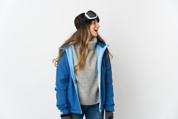 Fille de skieur avec des lunettes de snowboard sur blanc en riant en position latérale