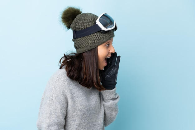 Fille de skieur de race mixte avec des lunettes de snowboard sur fond bleu isolé criant avec la bouche grande ouverte sur le côté.