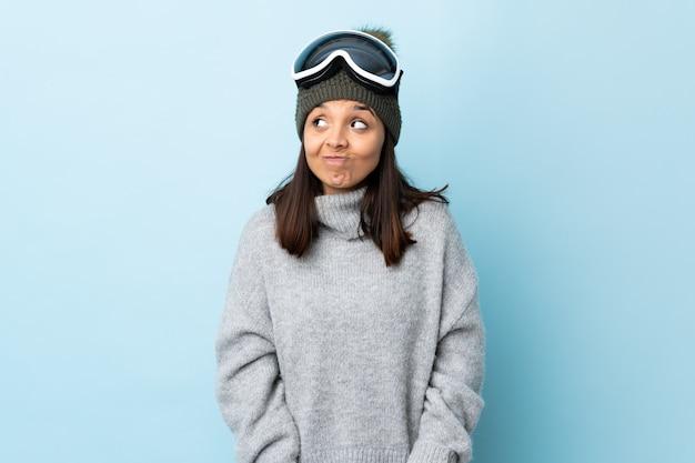 Fille de skieur de race mixte avec des lunettes de snowboard sur mur bleu ayant des doutes en levant les yeux.