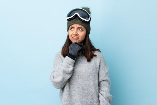 Fille de skieur de race mixte avec des lunettes de snowboard sur mur bleu ayant des doutes