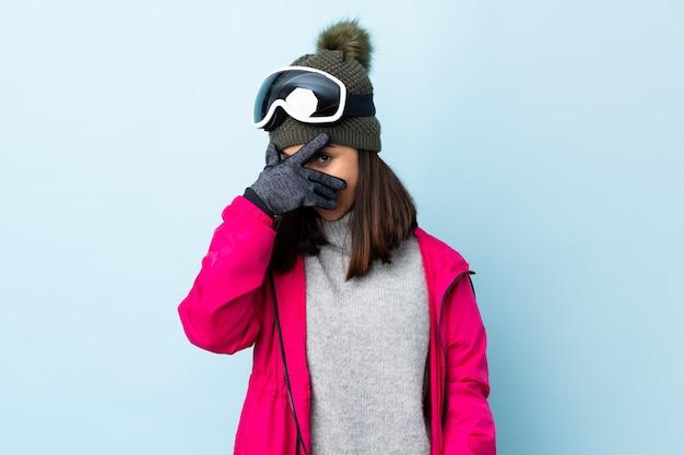 Fille de skieur de race mixte avec des lunettes de snowboard sur un mur bleu couvrant les yeux par les mains et souriant.