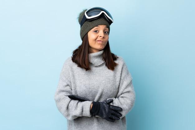 Fille de skieur de race mixte avec des lunettes de snowboard sur mur bleu faisant des doutes geste tout en soulevant les épaules.
