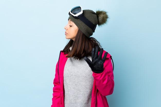 Fille de skieur de race mixte avec des lunettes de snowboard sur le mur bleu faisant un geste d'arrêt et déçu.
