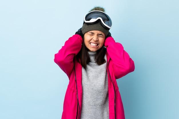 Fille de skieur de race mixte avec des lunettes de snowboard sur le mur bleu frustré et couvrant les oreilles.