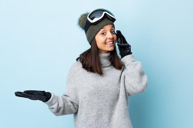 Fille de skieur de race mixte avec des lunettes de snowboard sur le mur bleu en gardant une conversation avec le téléphone mobile avec quelqu'un.