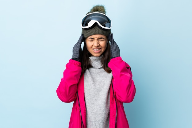 Fille de skieur de race mixte avec des lunettes de snowboard sur un mur bleu avec des maux de tête.