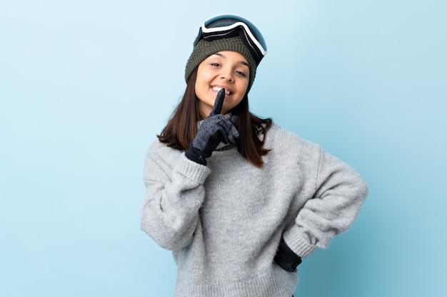 Fille de skieur de race mixte avec des lunettes de snowboard sur mur bleu montrant un signe de silence geste mettant le doigt dans la bouche.