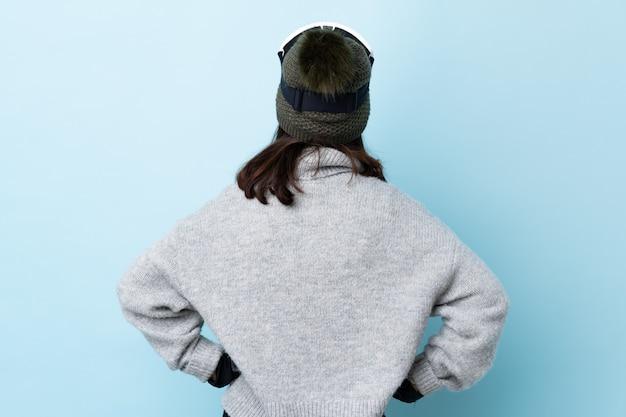 Fille de skieur de race mixte avec des lunettes de snowboard sur le mur bleu en position arrière.