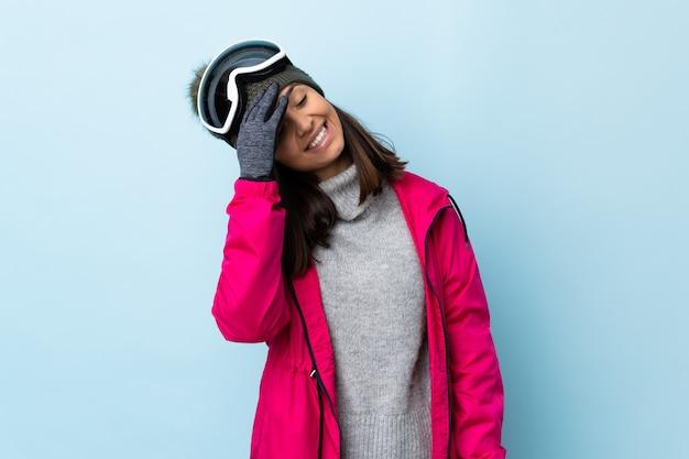 Fille de skieur de race mixte avec des lunettes de snowboard sur le mur bleu souriant beaucoup.