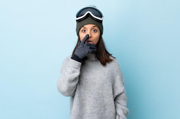 Fille de skieur de race mixte avec des lunettes de snowboard sur le mur bleu surpris et choqué tout en regardant à droite.