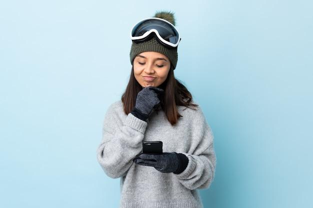 Fille de skieur de race mixte avec des lunettes de snowboard sur la pensée de mur bleu et l'envoi d'un message.