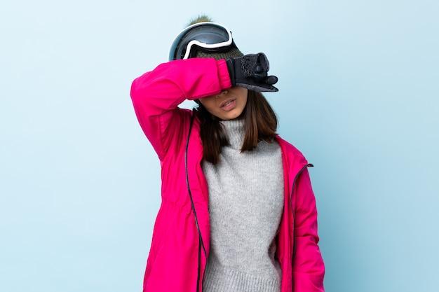 Fille de skieur de race mixte avec des lunettes de snowboard sur les yeux coniques bleus isolés par les mains
