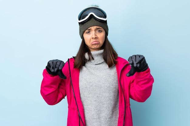 Fille de skieur de race mixte avec des lunettes de snowboard