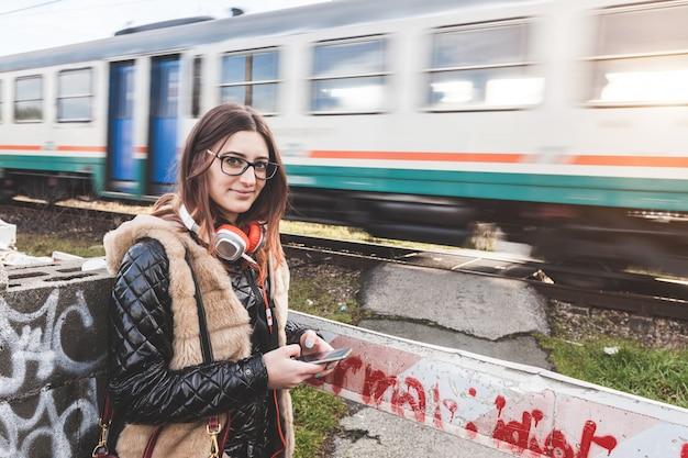 Fille avec smart phone avec train en passant.