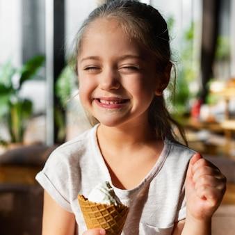Fille smiley coup moyen avec de la crème glacée