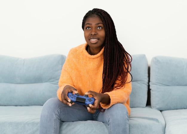 Fille de smiley jouant coup moyen de jeu vidéo