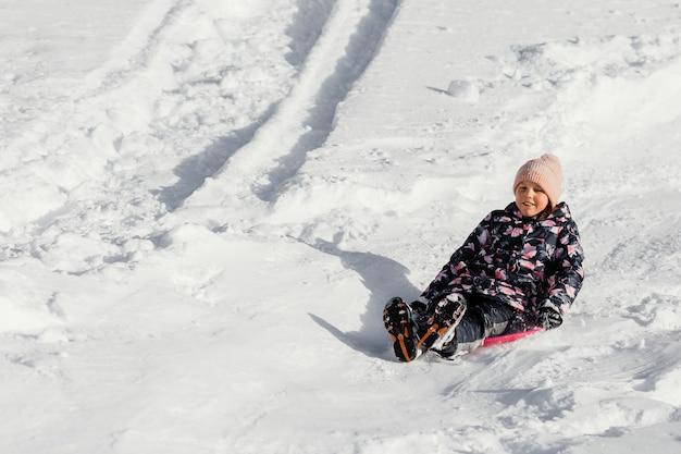 Fille smiley plein coup dans la neige à l'extérieur