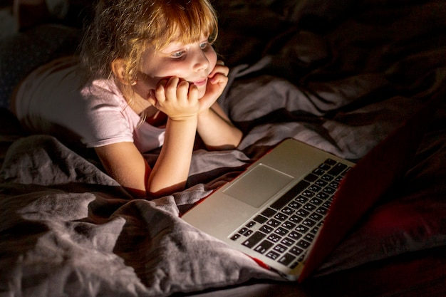 Fille de smiley vue de côté au lit avec un ordinateur portable