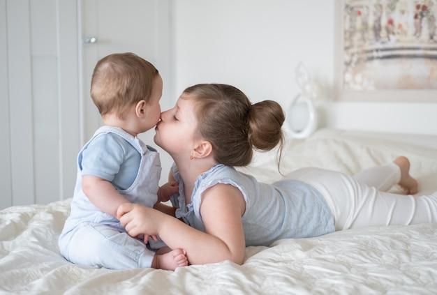 Fille sœur aînée embrassant son petit frère de bébé sur le lit à la maison.