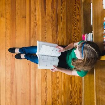Fille sur le sol, livre de lecture avec des graphiques