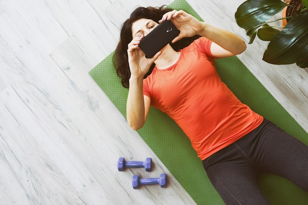 Une fille sur le sol regarde la formation en ligne par téléphone