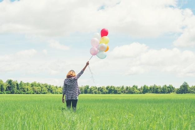Fille solitaire avec des ballons multicolores