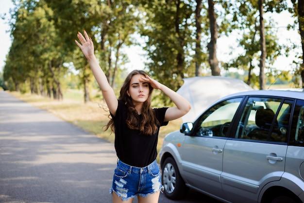 Une fille solitaire et confuse se tient près de sa voiture cassée avec le capot ouvert et arrête les autres conducteurs de demander de l'aide et de réparer la voiture