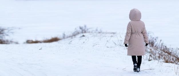 Fille solitaire dans un champ enneigé, promenade hivernale à l'extérieur