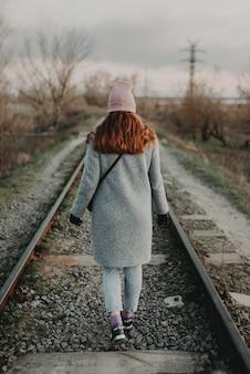 Une fille solitaire marche le long de l'ancienne voie ferrée