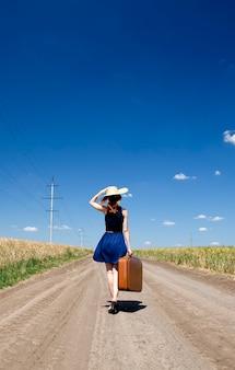 Fille solitaire avec valise à route de campagne.