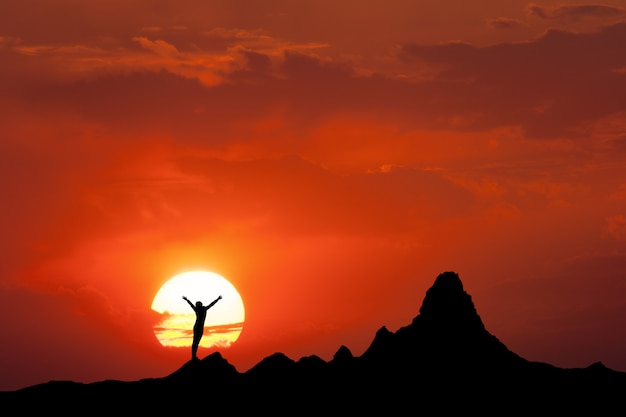 Fille sur le sommet de la montagne contre le soleil