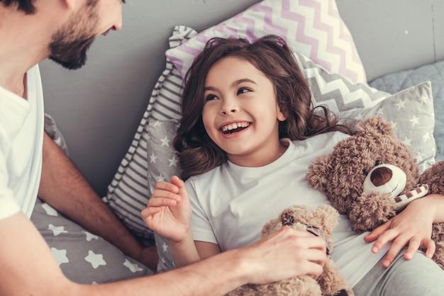 La fille et son beau jeune papa tiennent des ours en peluche.