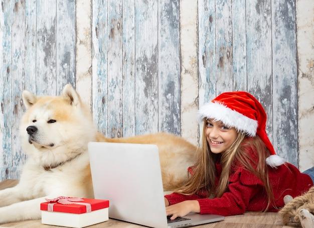Fille avec son chien à l'aide d'ordinateur à noël