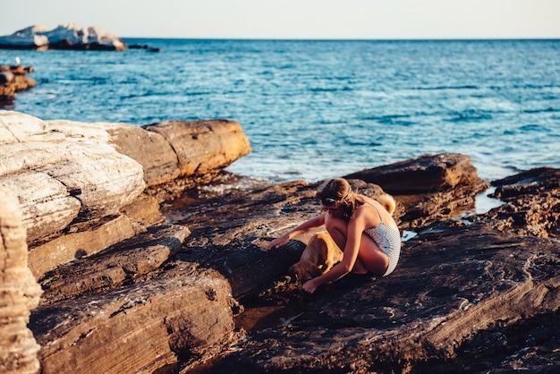 Fille et son chien explorant la plage rocheuse
